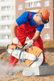Builder at cutting curb work. Construction worker at curb stone cutting work by cut-off saw with diamond wheel Royalty Free Stock Photo
