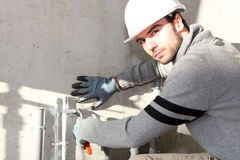 Builder cutting an outdoor pipe Stock Photography