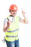 Builder with debit card and phone pointing up Royalty Free Stock Photography