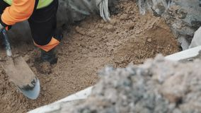 Builder digging pile of sand in ditch with shovel. Slowmotion stock footage