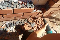 The builder dismantles the brick in the wall with a punch stock photography