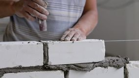 Builder is doing brickwork, hitting over brick by trowel for leveling and taking off an excess cement mortar. Close-up of his hands stock footage
