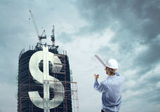 Builder and downtown with dollar Royalty Free Stock Image