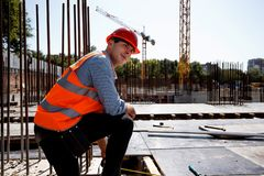 Builder dressed in orange work vest and helmet has a rest on the open building site stock photography