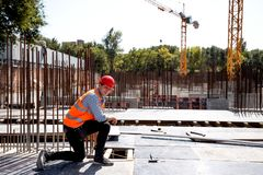 Builder dressed in orange work vest and helmet uses a tape measure on the building site royalty free stock image