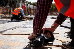 Builder dressed in orange work vest and helmet is using a circular saw on the open building site stock photo