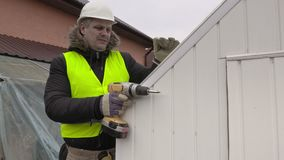 Builder with drill. In autumn day stock video footage