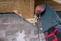 Builder with Drill Building Stairs in Basement Stock Photos