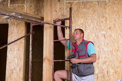 Builder with Drill Climbing Ladder of Scaffolding Royalty Free Stock Photos