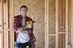 Builder with drill in partially built house, portrait Stock Images