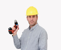 A builder with a drill. A builder wearing a yellow hardhat and holding a cordless drill Stock Photos