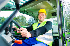 Builder driving construction machinery Stock Photography