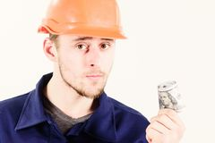 Builder earn money, repairman holds cash, banknotes in hand. Illegal construction, concept. Handyman with strict face, white background. Man in helmet got royalty free stock photography