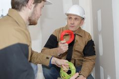 Builder engineer and co-worker screwing equipment in fuseboard. Builder engineer and his co-worker screwing equipment in fuseboard Royalty Free Stock Photos