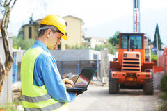 Builder engineer with laptop at construction site Royalty Free Stock Image