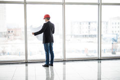 Builder engineer wear security helmet look at blueprint paper construction near panoramic windows Stock Photo