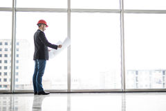 Builder engineer wear security helmet look at blueprint paper construction near panoramic windows Royalty Free Stock Images