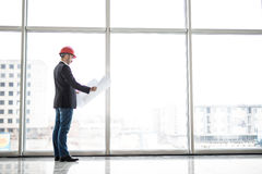 Builder engineer wear security helmet look at blueprint paper construction near panoramic windows Stock Image