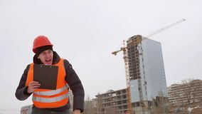 Builder evil architect man worker shakes hands in helmet and orange vest against the background of a multi-storey winter. Builder evil architect man worker stock video