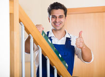 Builder examines stairs railing with spirit level Stock Image