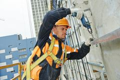 Builder at facade construction work. Worker builder making construction for ventilation facade on a building with screwdriver drill Royalty Free Stock Photos
