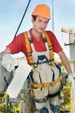 Builder facade painter. Young smiling painting facade builder worker with roller in work wear Stock Photo