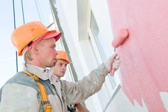 Builder facade painters at work. Builder worker painting facade of building house with roller Royalty Free Stock Photography