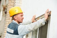 Builder facade plasterer worker with level Stock Photos