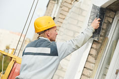 Builder facade plasterer worker Stock Photo