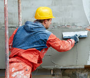 Builder at facade plastering works Stock Images
