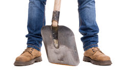 Builder feet with a shovel between Stock Photography