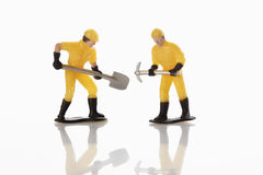 Builder figurines with shovel and pick axe on white background Stock Photos