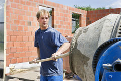 Builder filling a conrete mixer. Builder working with a concrete mixer. Spade in hand Royalty Free Stock Photography