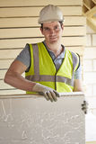 Builder Fitting Insulation Boards Into Roof Of New Home Stock Images