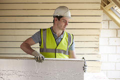 Builder Fitting Insulation Boards Into Roof Of New Home Royalty Free Stock Photography