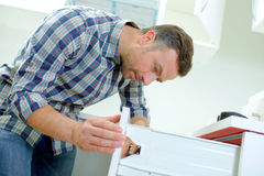 Builder fitting kitchen draw. Builder fitting a kitchen draw Royalty Free Stock Photos