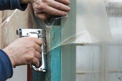 Builder fixes polyethylene film with staple gun Royalty Free Stock Photos