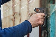 Builder fixes polyethylene film with staple gun Stock Images