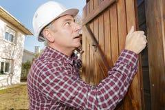 Builder fixing shed door Stock Photos