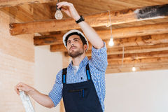 Builder fixing socket using ladder indoors Stock Photos