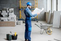 Builder at the construction site. Builder or foreman in working uniform expertising the structure standing with blueprint at the construction site indoors royalty free stock photos