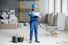 Builder at the construction site. Builder or foreman in working uniform expertising the structure standing with folder at the construction site indoors stock images