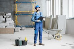 Builder at the construction site. Builder or foreman in working uniform expertising the structure standing with folder at the construction site indoors royalty free stock photography