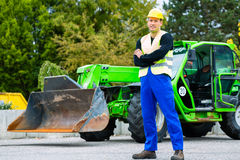 Builder in front of  construction machinery Royalty Free Stock Photo