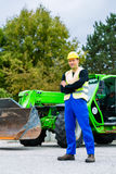 Builder in front of  construction machinery Stock Image