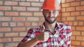 Builder gestures good quality at the building under construction. Young builder gesturing good quality at the building under construction. Close up of caucasian stock footage