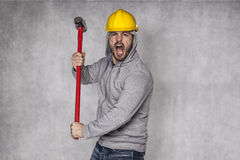 Builder on a grey background, holding a hammer and shouting Stock Image