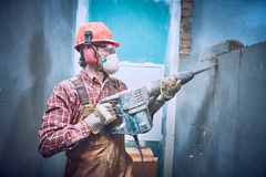 Builder with hammer breaking wall indoors. Worker in personal protection equipment with demolition hammer at interior brick wall construction breaking in Royalty Free Stock Image