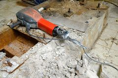 Builder with a hammer. Builder with hammer drill concrete on a construction site Stock Photography