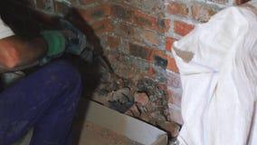 Builder with hammer drill. Man breaks wall. Broken hammer drill. Home construction. Builder destroys bricks.  stock video